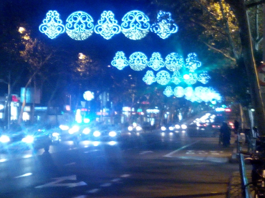 Bluish white Yuletide Lighting decors shine down upon the busy street of Bravo Murillo