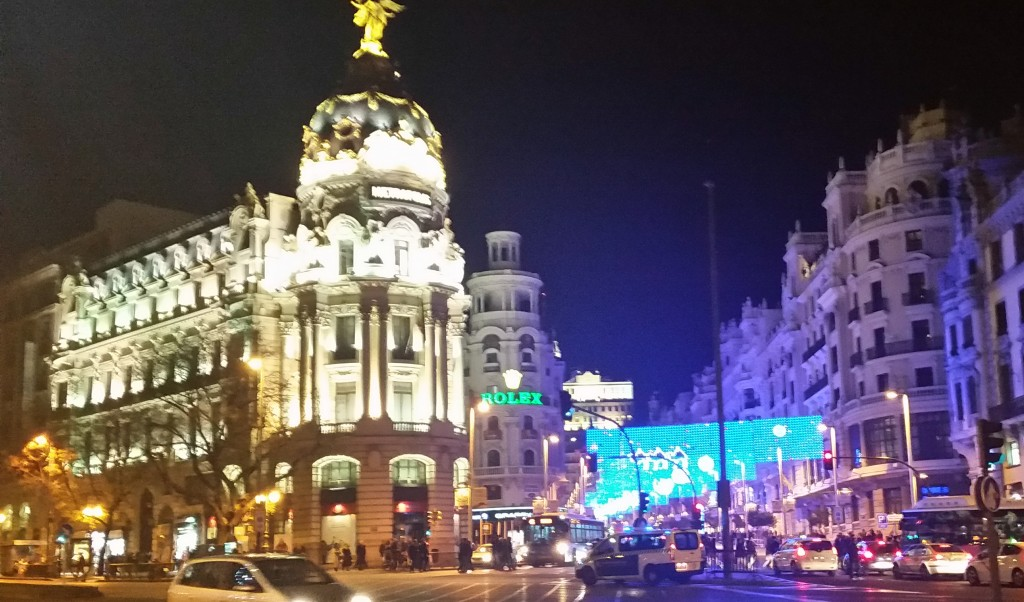 Imposing buildings at night. Metropolitan, along Calle de Alcala and Rolex Building at Gran Via, as viewed from Calle de Alcala